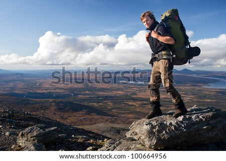 Hiker with huge backpack on the mountain top