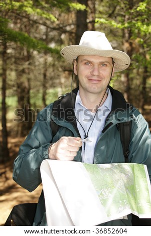 Hiker with map and compass in forest