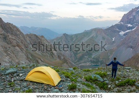 Hiker with walking poles and climbing tent.\ Man observing scenic evening view of mountain valley yellow camping tent on grassy rocky place
