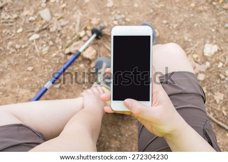 Hiker woman asking medical help with your phone after an accident