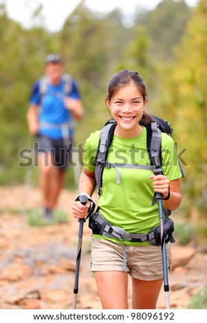 Hiker woman. Hiking asian woman walking with hiking poles and hiking backpack smiling happy outdoors in nature. Hiker in background.