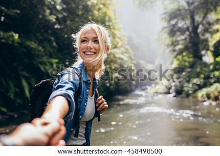 Hiker woman holding man's hand and leading him on nature outdoor. Couple in love. Point of view shot.