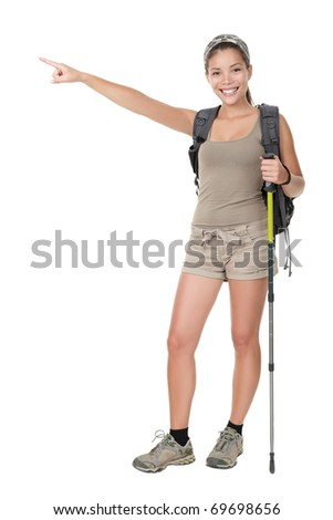 Hiker woman standing isolated. Female hiker pointing. Young woman wearing backpacking bag and hiking poles. Isolated on white background in full length.