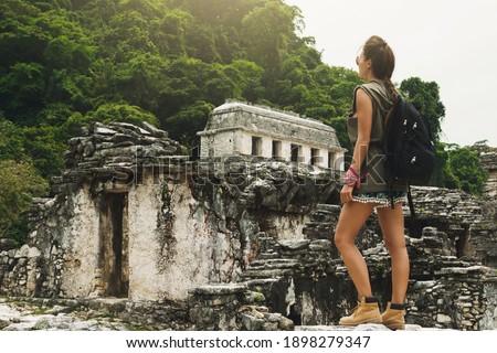 Hiker woman with a backpack looking at ancient Mayan ruins Foto stock ©