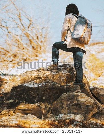 Hiker woman with backpack go up on rock, rear view. Hiking and recreation theme