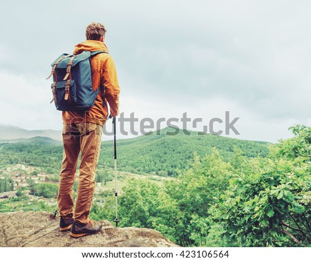 Hiker young man with backpack and trekking poles standing on edge of cliff and looking at the mountains in summer outdoor, rear view
