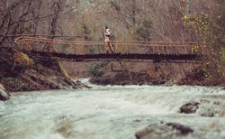 Hiker young woman crossing mountain river on a bridge in forest