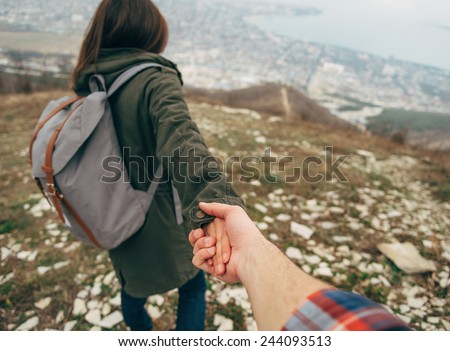 Hiker young woman holding man\'s hand and leading him on nature outdoor. Couple in love. Point of view shot. Focus on hands.