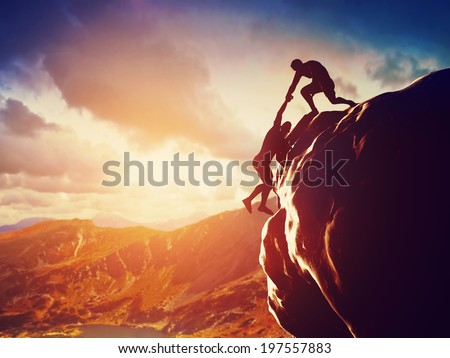 Hikers climbing on rock, mountain at sunset, one of them giving hand and helping to climb. Help, support, assistance in a dangerous situation - stock photo
