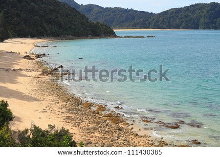 Hikers hiking in the distance on a beautiful sandy beach of Abel Tasman National Park, New Zealand - stock photo