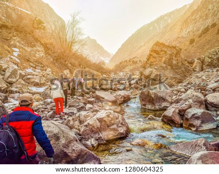 Hikers in the mountains. Group people backpackers tourists climbing struggling ascending rock mountain ridge travel tourism destination hiking. #1280604325