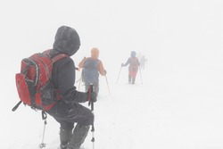 Hikers in the winter mountains in bad weather and poor visibility