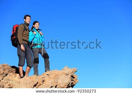 Hikers looking at view. Hiking young couple enjoying view looking at blue sky during hike. Multiracial couple with a lot of copy space.