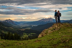 Hikers overlooking Crested Butte Valley at sunset