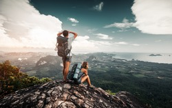 Hikers relax on top of a mountain and enjoy valley great view