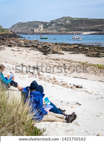 Hikers sit on a beach and examine their guide books and maps before heading off to explore the landscapes, seascapes and castles of Bryher and Tresco Islands, Isles of Scilly, Cornwall.
