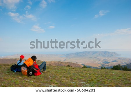 Hikers sit on the slope and enjoy the scenery