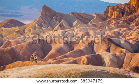 hikers standing in front of beautiful inspiring landscape - death valley national park