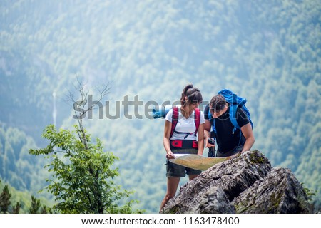 Hikers using map to navigate outdoor #1163478400
