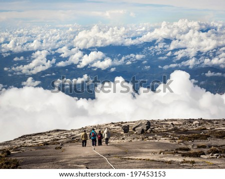 Hikers walking above the clouds at the top of Mount Kinabalu in Sabah, East Malaysia.