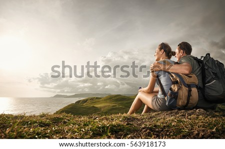 Hikers with backpacks relaxing on top of a hill and enjoying view of sunset in ocean.
