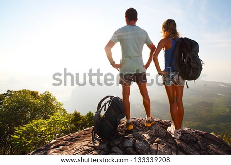 Hikers with backpacks relaxing on top of a mountain and enjoying valley view