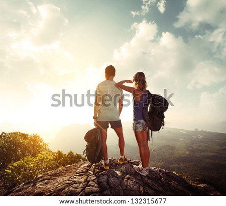 Hikers with backpacks standing on top of a mountain and enjoying sunrise #132315677