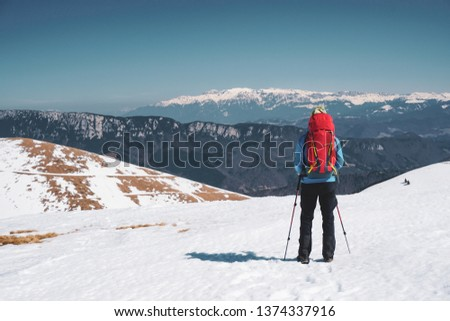 Hiking - back shot of male hiker with red backpack admiring the view of BUcegi mountains in winter / early spring in Romania, Iezer-Papusa mountains