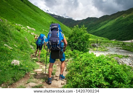 Hiking. Backpackers hiking in mountains. Mountain trekking. Men with backpacks on trek #1420700234