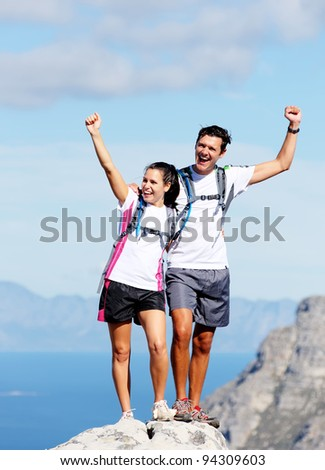 Hiking couple happy to reach the top of a mountain, healthy happy outdoor lifestyle