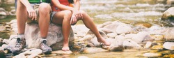 Hiking couple hikers resting on rock putting barefoot feet in water. Woman and man hiker sitting by river creek, boots footwear legs closeup. Young couple trekking, relaxing after hike, USA travel.