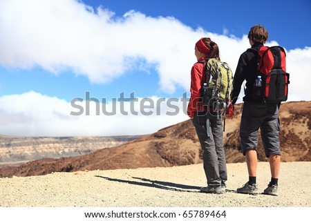 Hiking couple looking at the view holding hands in Teide National Park, Tenerife -  Copy space. Image from the volcano on the hiking path to Montana Blanca.