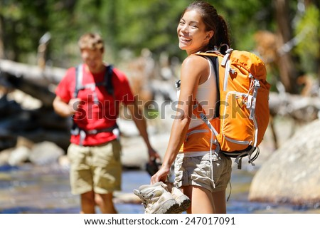 Hiking friends having fun crossing river in forest. Young happy adults barefoot walking in water with wet feet on an adventure trip hike in nature.