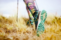 Hiking girl in a mountain meadow. Low angle view of generic sports shoe and legs on grass. Healthy fitness lifestyle outdoors.