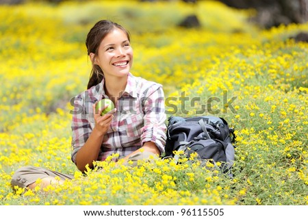 Hiking girl in spring sitting in forest floor flowers. Beautiful woman hiker smiling happy eating an apple during break. Mixed race Asian / Caucasian woman outdoor.