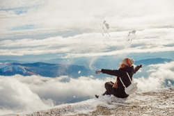 Hiking girl scattering snow and enjoy the fresh snow on a beautiful winter day in the mountains, the top of the mountain through the clouds in the background. Cold frozen winter activities.