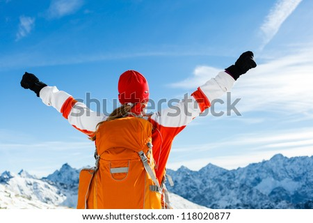 Hiking happy woman and success in mountains. Fitness and healthy lifestyle outdoors in winter nature. Motivation and Inspiration Concept, Raised Arms over Tatra Mountains landscape in Poland.
