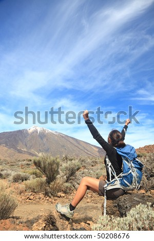 Hiking. Happy woman hiker with her arms raised up in the blue sky with lot's of copy space. From Teide, Tenerife