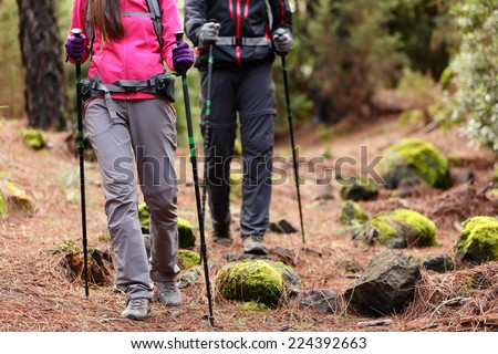 Hiking - Hikers walking in forest with poles on path in mountains. Close up of hiker shoes boots and hiking sticks poles. Man and woman hiking together. #224392663