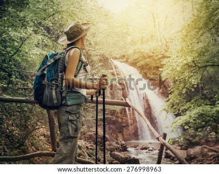 Hiking. Hikers woman with a backpack and a hat looking at a waterfall in the forest. stock photo