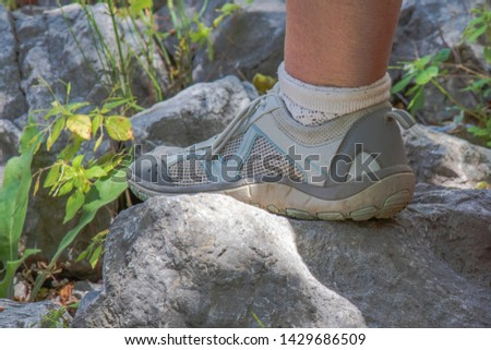 Hiking. Hiking shoes is on the stone. They helped to hike a lot of kilometers. Stone and grass wind and sun. Hiking is a great. #1429686509