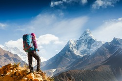 Hiking in Himalaya mountains. Woman Traveler with Backpack hiking in the Mountains. mountaineering sport lifestyle concept