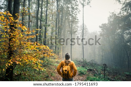 Hiking in misty morning at autumn forest. Woman tourist with knit hat and backpack standing at footpath in woodland