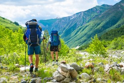 Hiking in mountains. Men hike in mountain trail. Tourists with backpacks walking on trek. Active leisure on vacation. Trekking in Caucasus.