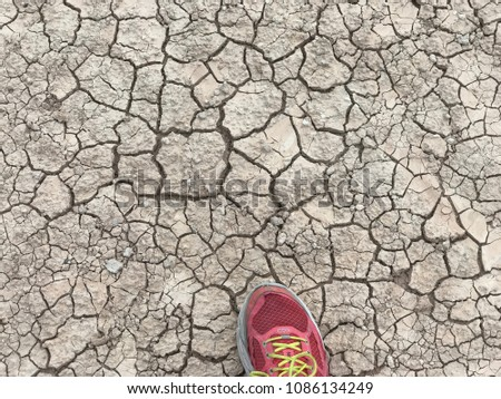 Hiking in the Badlands, one sees a stark contrast between a colorful running shoe and the monochromatic parched earth. #1086134249