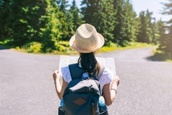 Hiking litle girl traveler at the crossroads with backpack checks map to find directions in wilderness area, real explorer - focus on hat - shallow depth of field. Travel Concept