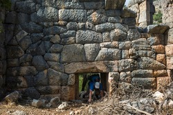 Hiking Lycian way. Man is trekking through low doorway of Pydnai Ruins, well-preserved polygonal masonry Pydnai was small naval and military base fortress, Outdoor activity in Turkey