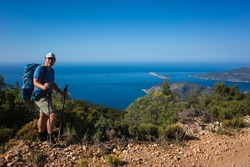Hiking Lycian way. Man tourist is standing on path over Mediterranean sea coast on Lycian Way trail on stretch between Kalkan and Kas, Trekking in Turkey, outdoor activity