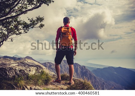 Shutterstock Hiking man, climber or trail runner in mountains, inspirational landscape. Motivated hiker with backpack looking at beautiful view. Trekking, travel and tourism concept. Fitness and healthy lifestyle.