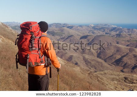 Hiking man with backpack and hiking poles looking at beautiful scenery